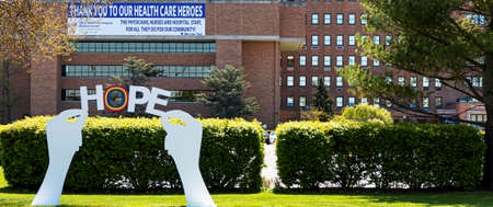 West Islip, New York, USA - 13 May 2020: Wooden sign of hands holding the words HOPE placed infront of Good Samaritan Hospital during the coronavirus COVID-19 pandemic.