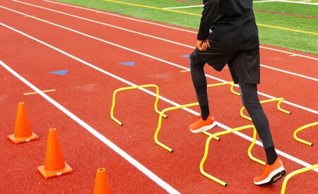 Rear view of a high school track and field athlete is running over yellow hurdles set up in lane on a red track.