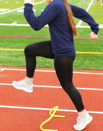 A high school female athlete is in the A-position stepping over a yello mini banana hurdle in lanes on a track.