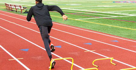 Rear view of a high school track and field sprinter running over yellow mini banana hurldes on a track during practice,
