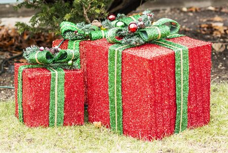 Three large red Christmas presant ornamets with green bows outside in front of a home on the grass.