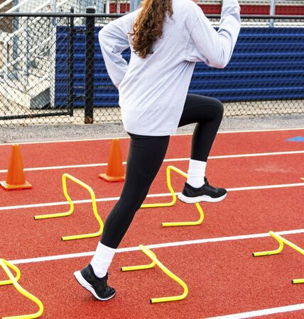 A high school girl is stepping over yellow mini hurdles during speed and agility practice on a track.