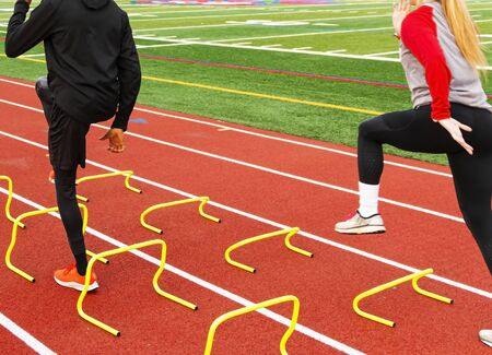 Rear view of male and a female athletes running over yellow mini hurdles set up in lanes on a red track at track and field practice.