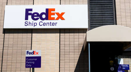 Melville, New York, USA - 13 May 2020: Building exterior of FedEx shiping center and sign for customer parking only.
