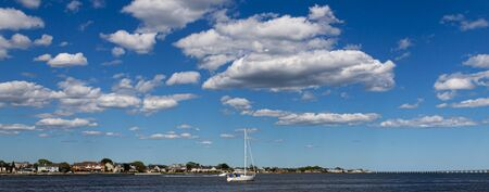 A sailboat in the Great South Bay with very blue sky and thick puffy white clouds above. Фото со стока