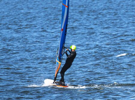 A man is enjoying windsurfing in the Long Island Sound on a Sunday morning.