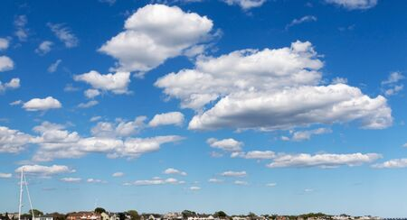 Thick white puffy clouds looking low over the horizon. Фото со стока