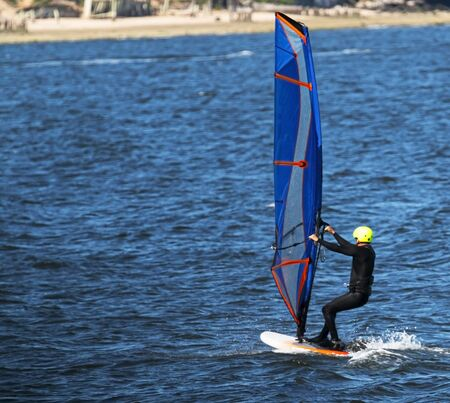 Rier view of a man windsurfing in the Long Island Sound on a cool June morning.