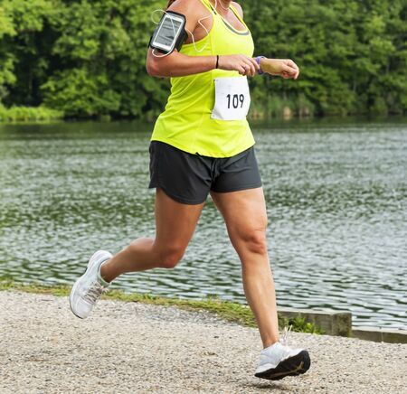 A runner is running a 10K race in Babylon Village wearing a cell phone on her arm passing southards pond in the summer. Reklamní fotografie