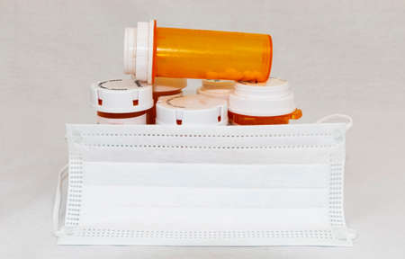 Babylon, New York, USA - 11 April 2020: A white surgical mask covering perscription medical bottles with opiods in them with a whte background.