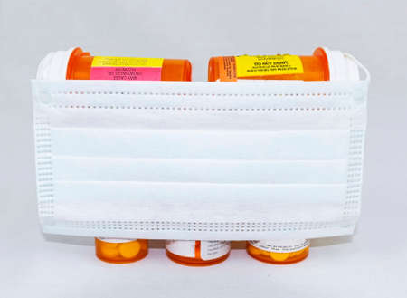 A white surgical face mask covering perscription medicine bottles with opiods in them with a whte background.