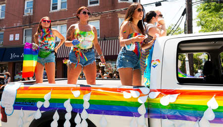 Babylon, New York, USA - 28 June 2020: Women waving gay pride flags while standing up in back of a truck during pride parade in Babylon Village.