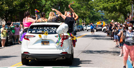 Babylon, New York, USA - 28 June 2020: Rear view of car in Gay pride car parade held in Babylon Village with people celebrating and waving to the crowd in cars and trucks.