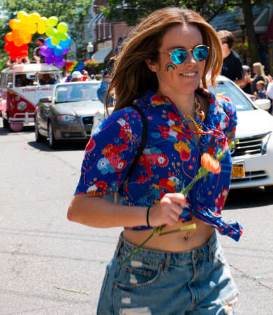 Babylon, New York, USA - 28 June 2020:Women smiling while running next to cars in the Gay Pride Car Parade handing our flowers to the crowd of supporters. Imagens - 152207838