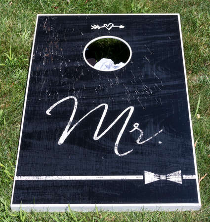 Black cornhole game board with Mr written in white text on a green lawn. Imagens