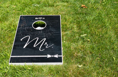 A black wooden Mr. Cornhole game board on a green lawn with copy space left on the right. Imagens