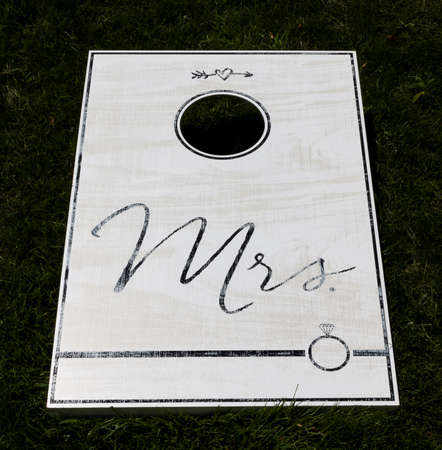 A wite cornhole game on a green lawn with Mrs written in black text. Imagens - 152411996