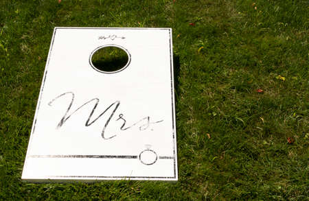 A white cornhole game on a green lawn with Mrs written in black as a wedding present. Imagens