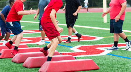 A high school football lineman is running an agility drill over red barriers ahile the coach is watching on a turf field.
