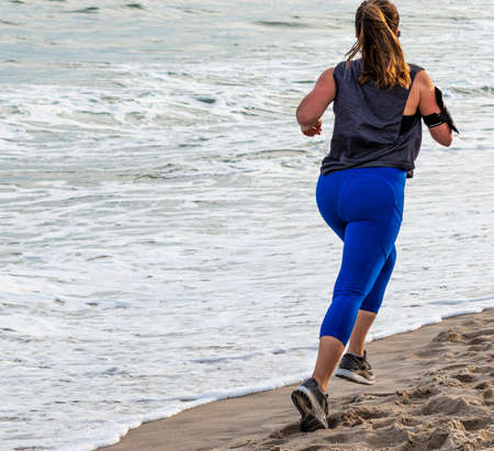A female in blue spandex is running at the beach close to the ocean on Fire Island.