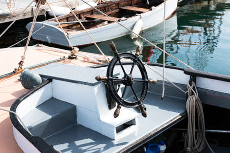 Front of boat with black iron steering wheel tied to a dock in Maine USA.