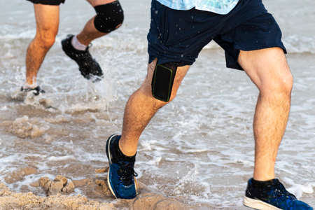 Runners splashing in the ocean running on the edge of the beach with one cell phone sticking out of shorts.
