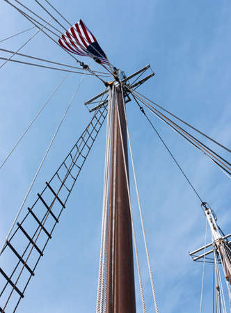 Looking up at An American Flag is on top of the mast of a sailboat.