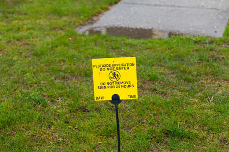 A small yellow sign is placed on the front lawn agter chemical pesticide was applied as a warning to do not enter.