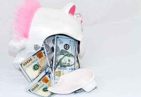 Money falling out of a broken piggy bank.