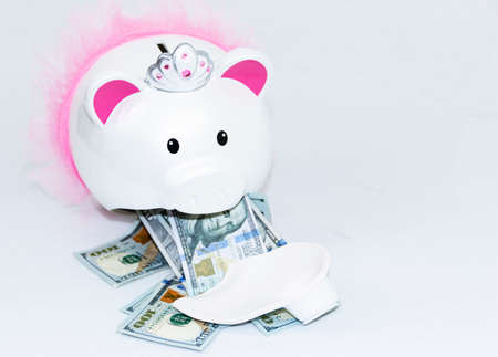 Front view of white piggy bank with pink ears and tutu broken with one hyndred dollar bills falling our of mouth.on a white background. Imagens