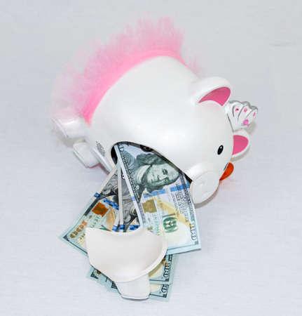 A white piggy bank lying on its side is broken with one hundred dollar bills spilling out.