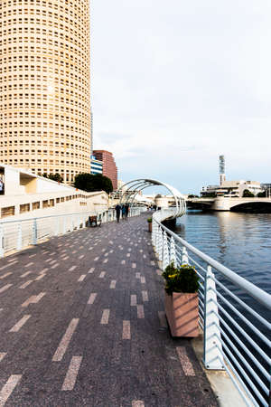 Tampa Florida USA riverwalk along the water with tall buildings on the left and copy space on the right.