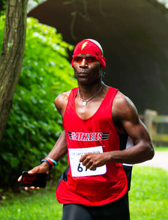 Babylon, New York, USA - 12 August 2018: An African American runner with red bandana with the flash sidn on it during the Dirty Sock 10K trail race. Imagens - 153843845