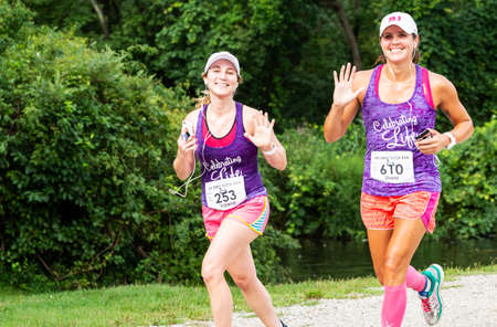 Babylon, New York, USA - 12 August 2018: Two women waving and smiling celebrating life during the Dirty Sock 10K trail race. Imagens - 153843844