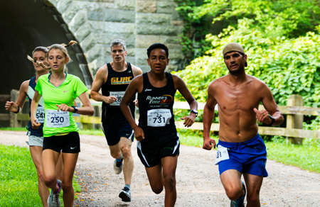 Babylon, New York, USA - 12 August 2018: Fast runners emerging from under the tunnel during the Dirty Sock 10K trail race. Imagens - 153843843