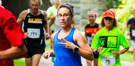 Babylon, New York, USA - 12 August 2018: A female runner giving the peace sign while running a 10K in the woods after running through a tunnel in a group of people. Imagens - 153843842