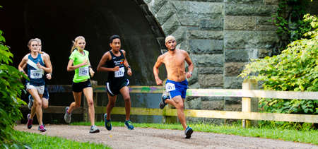 Babylon, New York, USA - 12 August 2018: Fast runners emerging from under a tunnel during the Dirty Sock 10K trail race.