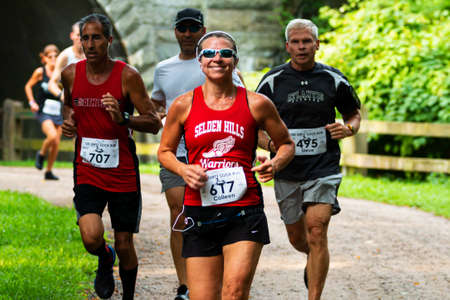 Babylon, New York, USA - 12 August 2018: Women smiling while running the Dirty Sock 10K trail race. in the woods after coming out of tunnel.