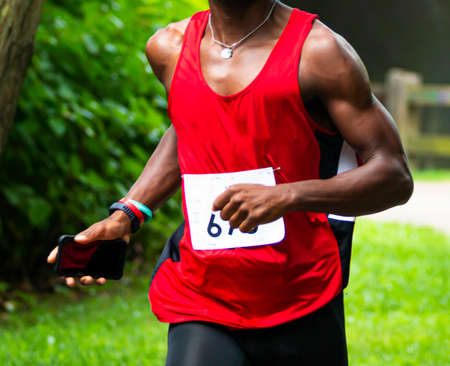 An African American runner with red uniform top on during the Dirty Sock 10K trail race in the woods.