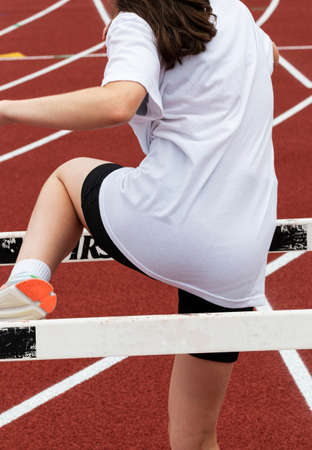 Young runner stepping over hurdles learning how to run over them. Imagens