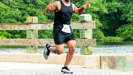 A runner racing in a trail 10K gives two peace signs while he is crossing a bridge over a lake in the woods. Imagens