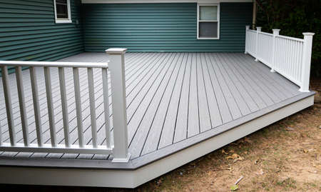 A new deck is installed on the back of a house with composite material and white hand rails. Imagens - 153884946