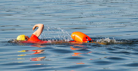 An individual swimmer is training in the bay wearing a red top, yellow bathing cap and an orange safety flotation device. Imagens - 153884999