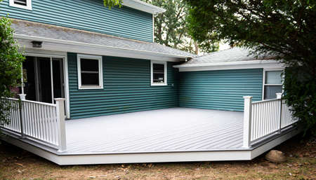 A new deck is installed on the back of a house with composite material and white hand rails. Imagens - 153884401