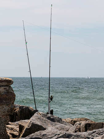 Two fishing poles on the rocks of a jetty on the coast of Fire Island New York,