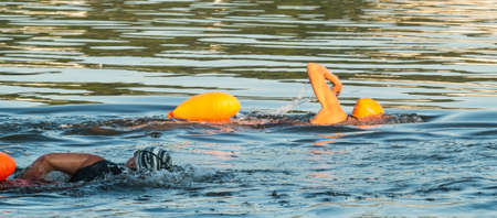 One caucasion and one African American swimmers swimming side by side training for triathlons in the sea.