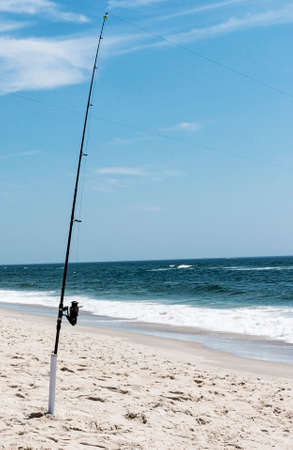 A fishing pole with its line cast in to the Atlantic Ocean standing upright in a holder in the sand on the beach on The Fire Island National Sea Shore.