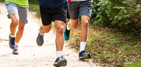 Front view of the legs of three high school boys running on a dirt path in a park. Imagens