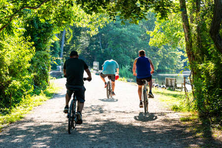 Three men on a casual bike ride on a dirt path in the woods leaving the shade into the hot sunshne.