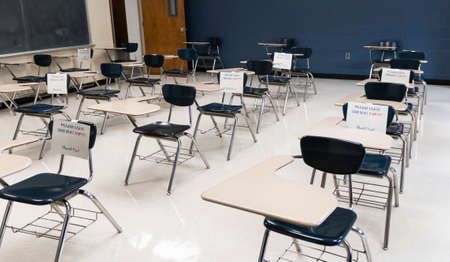 Desks in a high school classroom have sign reading fo not sit leave empty to help in makeing the room more socially distant to be abe to return to in school learning. Imagens